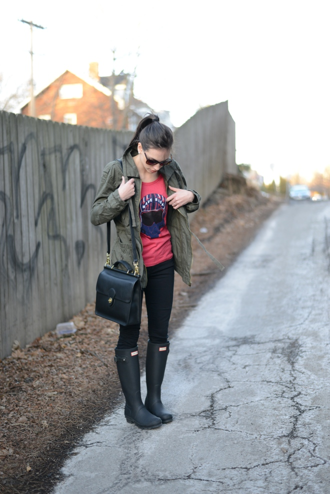 Maverick T Shirt styled by top US fashion blog, Wellesley & King: image of a woman wearing a red Maverick T Shirt, black Hunter rain boots, Coach bag, and a Macy's field jacket